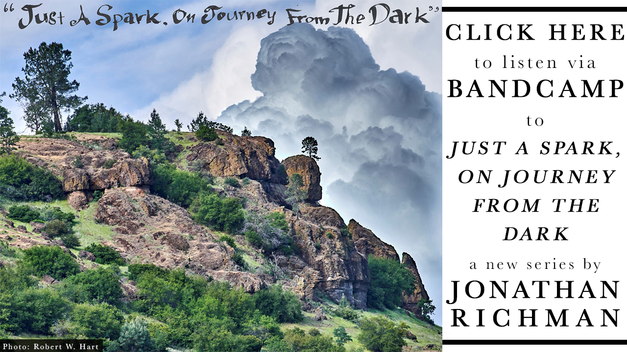 "beautiful image of a cliff and trees against a bright blue sky with massive clouds. across the sky in calligraphy style writing by Jonathan richman it says ""just a spark, on journey from dark"""